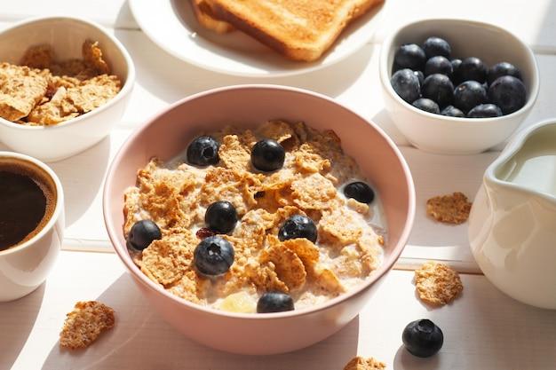 ミルクブルーベリーコーヒーと木製のテーブルの上のトーストのクローズアップと全粒小麦フレークの朝食