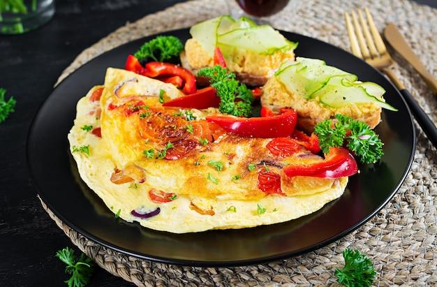 Завтрак. омлет с паприкой, сыром и помидорами с бутербродами на черной тарелке. фриттата - итальянский омлет.