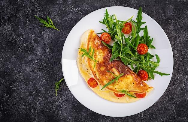 Завтрак. омлет с помидорами, сыром и салатом на белой тарелке. фриттата - итальянский омлет. вид сверху
