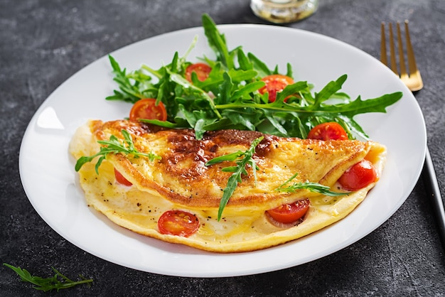 Breakfast. omelette with tomatoes, cheese  and salad on white plate.  frittata - italian omelet.