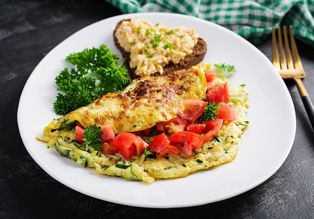 Breakfast. omelette with zucchini, cheese and tomatoes salad with sandwich on white plate.  frittata - italian omelet.