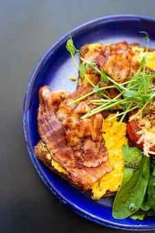 ベーコンと卵のプレートで朝食