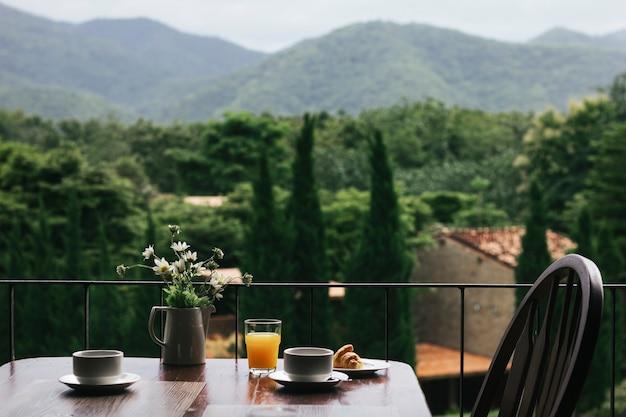 自然の景色を望む木製のテーブルで朝食