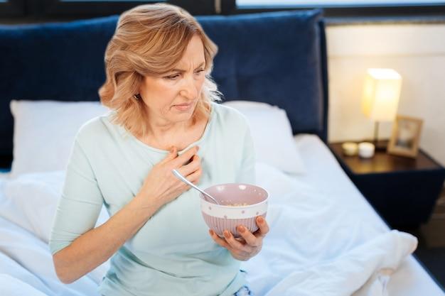 Завтрак в постели. довольно светловолосая зрелая женщина несет миску с кашей и плохо себя чувствует