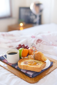 Breakfast on bed with coffee, croissants Window light