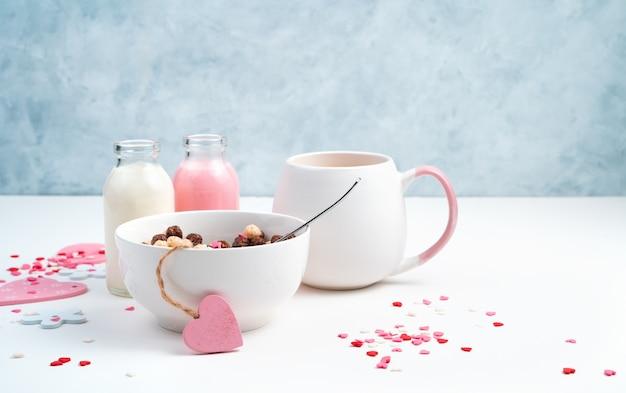 2月14日の朝食。シリアルボールとミルクドリンク、青と白の背景にハート。