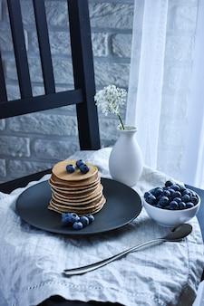 パンケーキと新鮮なブルーベリーと一緒にベッドで朝食