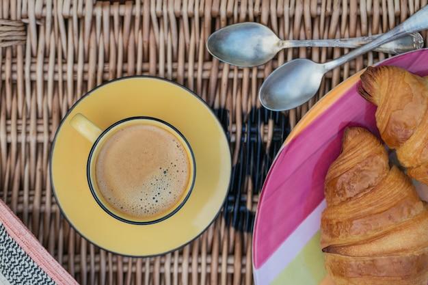 芝生での朝食。一杯のコーヒーとフレンチクロワッサン。ロマンチックな日付の背景。上面図