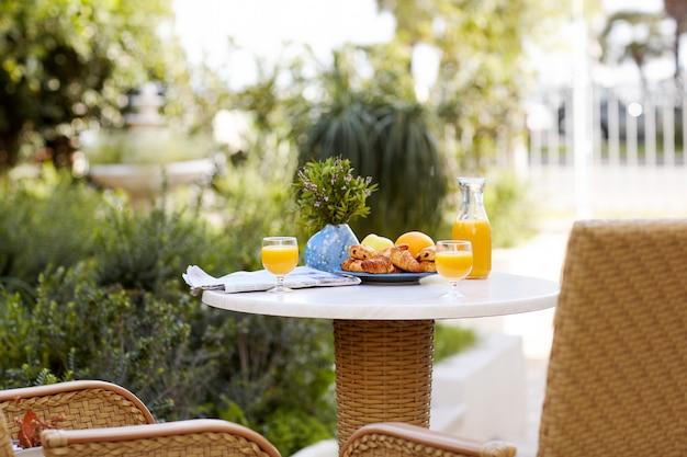 Завтрак на столе из свежего слоеного теста, круассанов, фруктов и свежевыжатого апельсинового сока