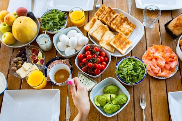 Завтрак на террасе, вид сверху семья, завтракающая на столе, яичница на лыжах