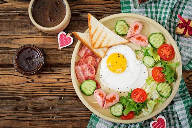 Завтрак на день святого валентина - жареное яйцо в форме сердца, тосты, колбаса, бекон и свежие овощи. английский завтрак. чашка кофе. вид сверху