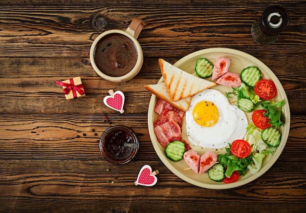 バレンタインデーの朝食-ハート型の目玉焼き、トースト、ソーセージ、ベーコン、新鮮な野菜。イングリッシュブレックファースト。一杯のコーヒー。上面図