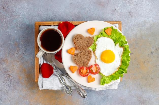 Завтрак в день святого валентина - яичница и хлеб в форме сердца и свежие овощи.