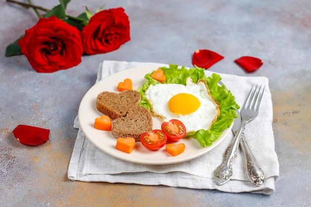 발렌타인 데이에 아침 식사-달걀 프라이와 심장 모양의 빵과 신선한 야채.