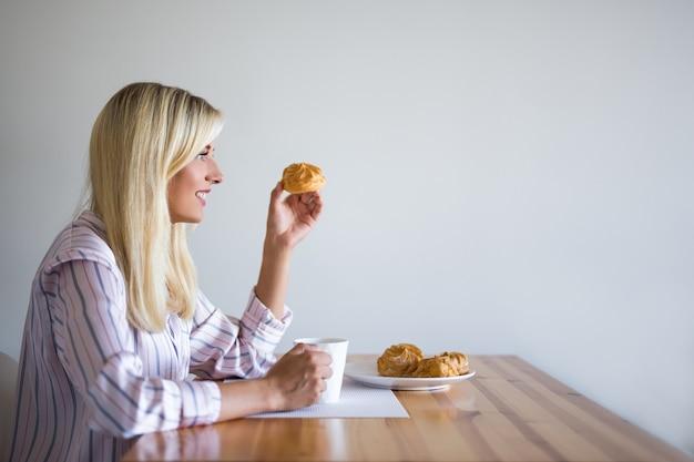 朝食またはコーヒーブレイクの概念-自宅でペストリーとコーヒーを飲む若い女性