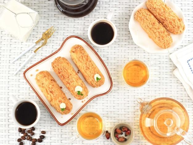 朝食またはティータイムのコンセプト、紅茶、コーヒー、クラケリンエクレア。上面図、白織りテーブルのフラットレイ構成