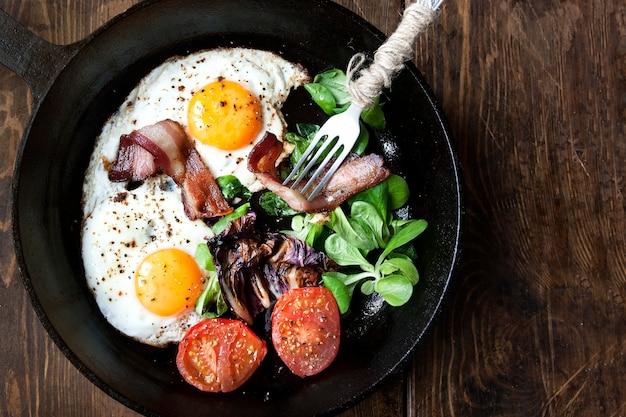 베이컨, 토마토 나무 배경에 튀긴 계란의 아침 식사 팬