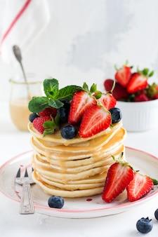 朝食のパンケーキ。明るいスレート、石またはコンクリートの背景にイチゴとブルーベリーのボウルとプレートに新鮮なブルーベリーとイチゴのパンケーキのスタック。上面図。コピースペース