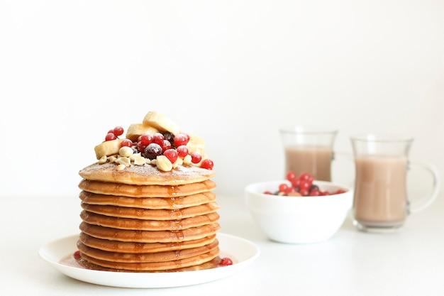 ベリーとココアを背景に、ベリーの朝食パンケーキが積み上げられています。