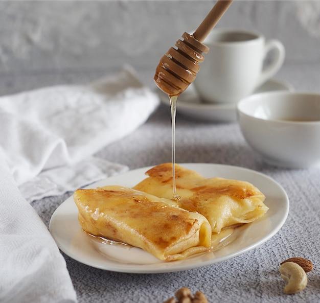 朝ごはん。皿に蜂蜜が入ったパンケーキ、その隣にはタオルがあります。蜂蜜のボウルとコーヒーのマグカップの後ろ。