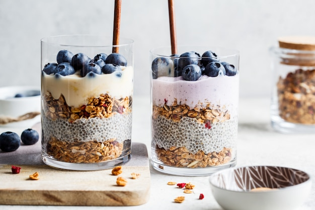 Breakfast parfait with chia, granola, berries and yogurt in a glass. layer dessert in glass.