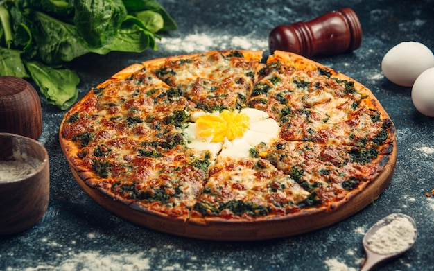 Breakfast pizza with pesto sauce and sunny side up egg in the middle