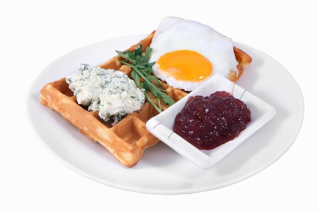 Breakfast on plate, belgian waffles with fried egg, cream cheese with dill, and cherry jam, isolated image on white background, no body.