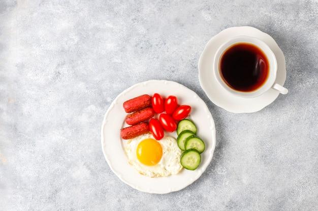 Un piatto da colazione contenente salsicce da cocktail, uova fritte, pomodorini, dolci, frutta e un bicchiere di succo di pesca.