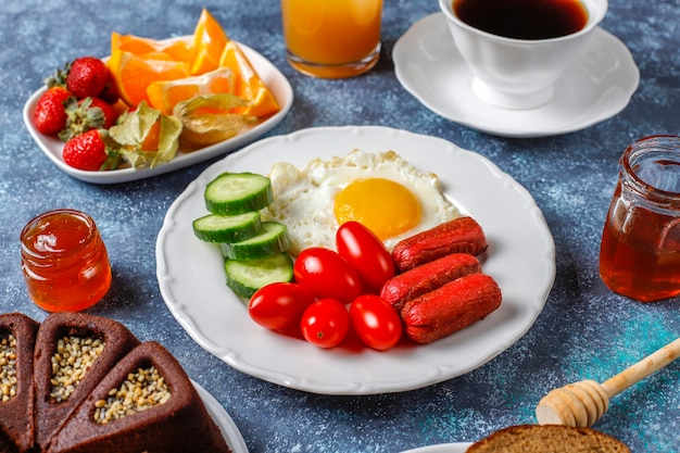 A breakfast plate containing cocktail sausages,fried eggs,cherry tomatoes,sweets,fruits and a glass of peach juice.