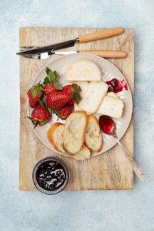 Тарелка для завтрака с сыром, хлебом, клубникой и джемом