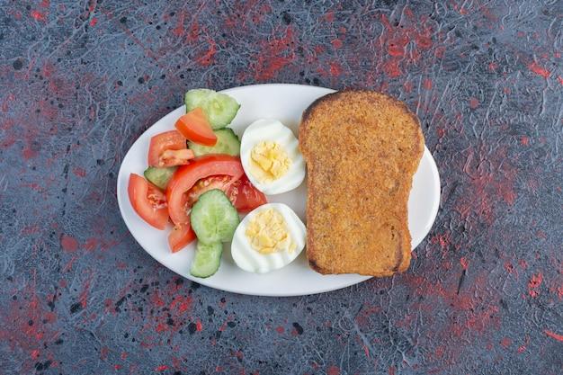 Тарелка для завтрака с яйцом, огурцом, помидорами и ломтиками хлеба.