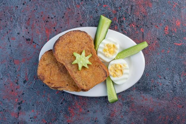 卵、きゅうり、パンのスライスが入った朝食プレート。