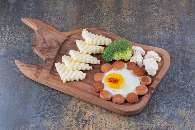 Piatto da colazione con uova fritte, salsicce e altri ingredienti