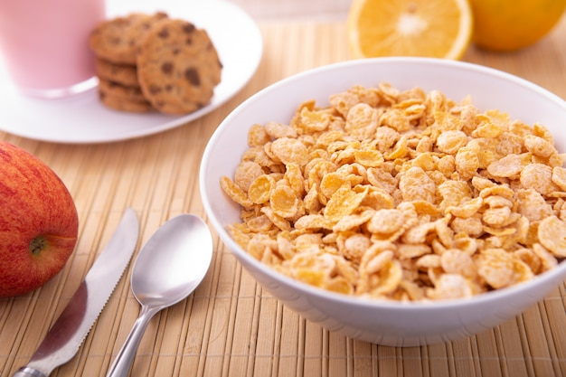 Breakfast pouring milk into corn flakes creating splash apple and orange fruit
