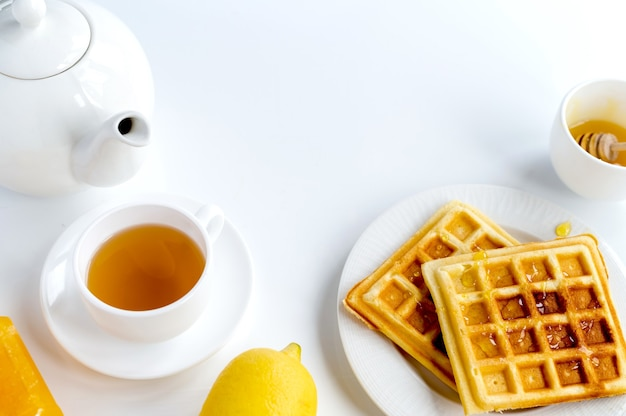 Breakfast products composition. waffles, tea and lemon. white background