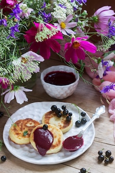 Breakfast of quark pancakes, black currant custard, currants and a bouquet of wild flowers on a wooden background.