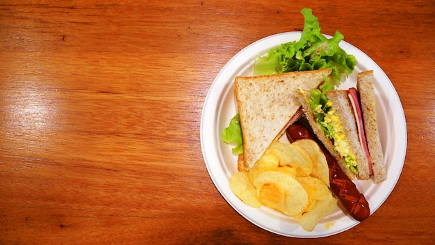 Breakfast at the restaurant. sandwich, sausage and potato chips in the white paper plate.