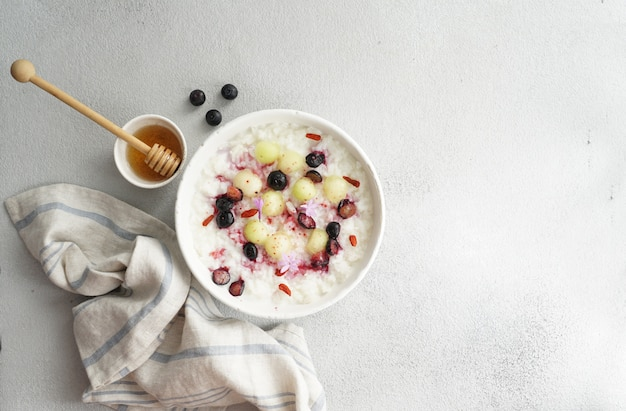 Breakfast rice porrige  with honey and melon, berries