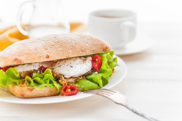 Breakfast in a rustic style on a white wooden surface. ciabatta with poached egg and grain mustard with a hot cup of coffee and fresh