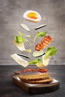 Breakfast sandwich in levitation on cutting board