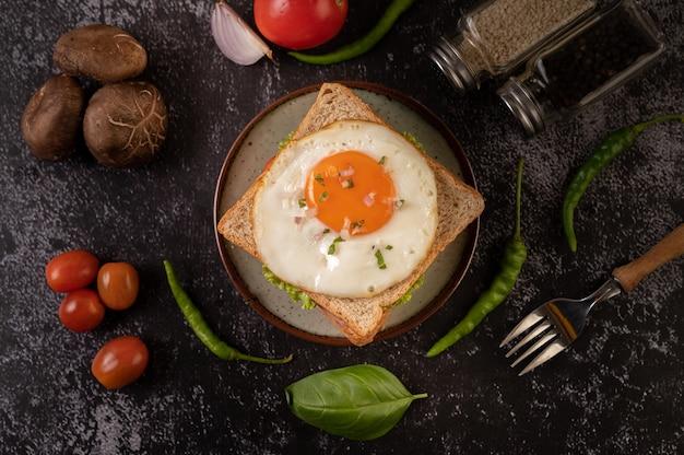 빵, 계란 후라이, 햄, 양상추로 만든 아침 샌드위치.