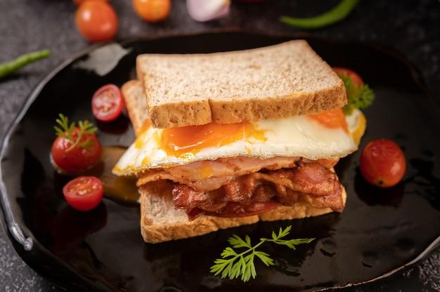 パン、目玉焼き、ハム、レタスで作った朝食サンドイッチ。