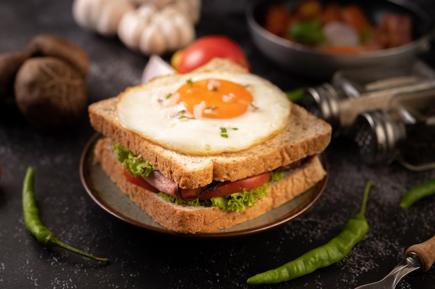 Breakfast sandwich made with bread, fried egg, ham, and lettuce.