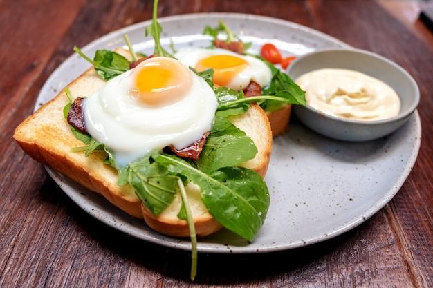 木製のテーブルの上のプレートに卵、ベーコン、サワークリームと朝食サンドイッチ