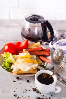 Breakfast sandwich with sausage, coffee and tomato