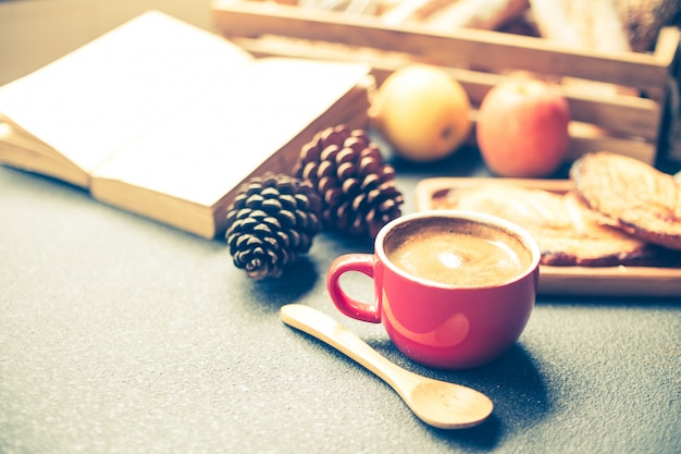 Breakfast scene with coffee cup, bread and fruits on the table. vintage tone