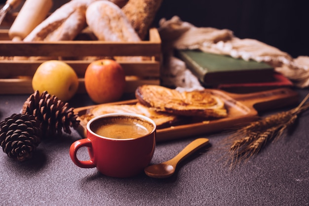 Breakfast scene with coffee cup, bread and fruits on the table