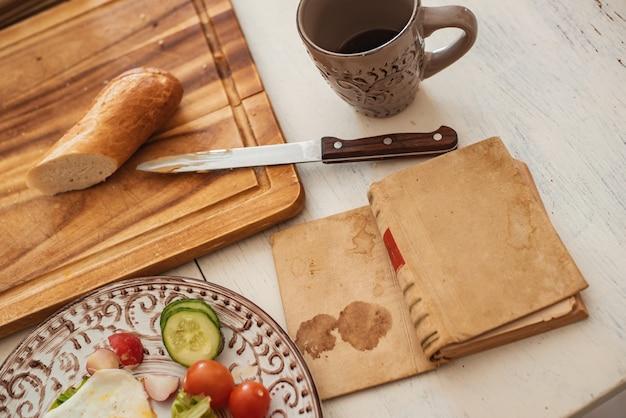 Завтрак подается в постель - вареное яйцо, свежий апельсин, печенье и кофе, пока вы читаете книгу и обнимаете кошку. выборочный фокус. тонированное изображение