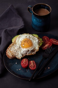 Breakfast served with coffee, bread, fried eggs, avocado and tomatoes
