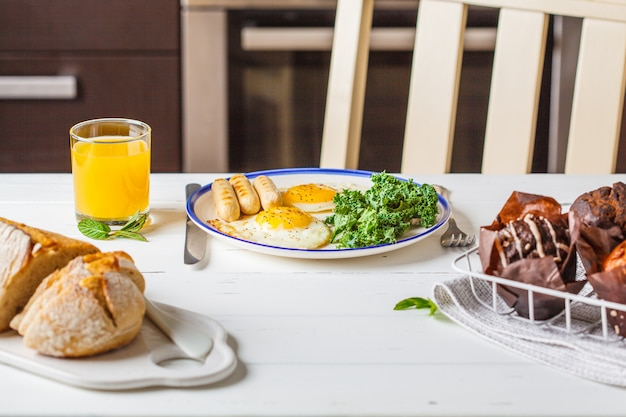 Breakfast served with fried eggs, salad, muffins and orange juice on white wooden table.